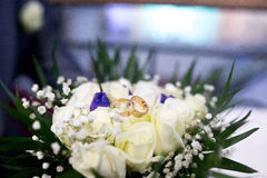 Bouquet and Two Wedding Rings. Golden jewelry, white roses. This photo is perfect for magazines, shops dealing with wedding ceremonies, marriage, jewellery Stock Photo