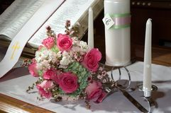 Bouquet with Unity Candle and Bible. Wedding Bouquet resting on the alter with a Unity Candle set and Bible open to Scripture Stock Photo