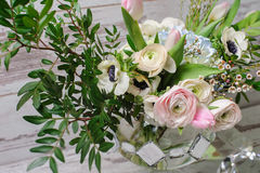 Bouquet  in vase of glass. Close up of bouquet of ranunculus, anemones and other flowers in a vase of glass stands on the background of vintage floor Stock Image