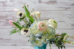 Bouquet  in vase of glass. Close up of bouquet of ranunculus, anemones and other flowers in a vase of glass stands on the background of vintage floor Royalty Free Stock Photography