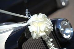 Bouquet on vintage wedding car. White ribbon bouquet on front of vintage wedding car Royalty Free Stock Photo