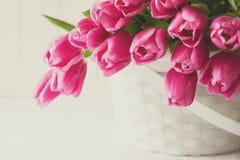 Bouquet violet de tulipes dans le panier devant le mur en bois blanc Image libre de droits