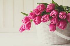 Bouquet violet de tulipes dans le panier devant le mur en bois blanc Images stock