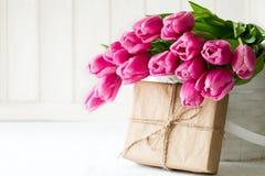 Bouquet violet de tulipes dans le panier devant le mur en bois blanc Photo libre de droits