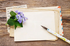 Bouquet of violet flowers (viola odorata) and vintage letters Royalty Free Stock Photo