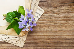 Bouquet of violet flowers (viola odorata) and vintage letters Stock Photos