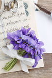 Bouquet of violet flowers (viola odorata) and vintage letters Royalty Free Stock Photos
