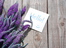 Bouquet of violet wild summer flowers and the blue card with the inscription Hello! Stock Photo