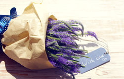 Bouquet of violet wild summer flowers and the blue card with the inscription With love on the wooden background Stock Photo