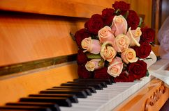 A bouquet of wedding flowers on the piano keys. royalty free stock photo