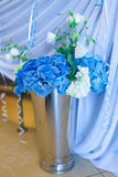 Bouquet of white and blue flower in metal vase Stock Photos