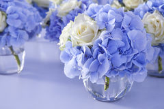 Bouquet of white and blue flower in vase. Of glass. Decoration of dining table Royalty Free Stock Photography