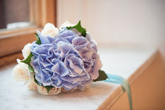 Bouquet of white and blue hydrangeas, tied with a ribbon, on the window sill Stock Images