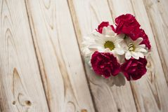 Bouquet of white chamomile and red carnation in vase on a wooden background with the place for your text. Bouquet of white chamomile and red carnation in vase Royalty Free Stock Photography