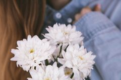 Bouquet of white chrysathemums with blurred background for wallpaper. Space for your text. Bouquet of white chrysathemums in girl`s hands with blurred royalty free stock photos