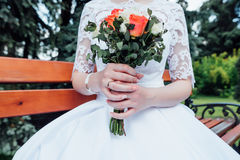 A bouquet of white and coral roses in the bride`s hands. A bouquet of white and coral roses in the hands of the bride in a white dress sitting on a bench Stock Photography