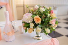 A bouquet of white, cream and pink roses stands in a vase. On the table next to a bottle decorated with lace and ribbon Stock Photo