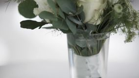 Bouquet of white flowers with big green leaves in glass vase put on white table. Beautiful bouquet of white flowers with big green leaves in glass vase put on stock footage