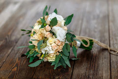 Bouquet of white flowers, creamflowers and greens lying on a woo Stock Photo