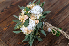 Bouquet of white flowers, creamflowers and greens lying on a woo Royalty Free Stock Images