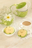 Bouquet of white flowers, cup coffee with milk and apple shaped cookies Royalty Free Stock Images