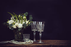 Bouquet of white flowers, pearl beads and wine glasses on a blac Royalty Free Stock Image