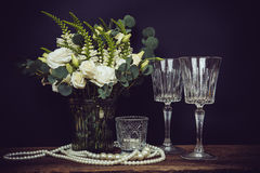 Bouquet of white flowers, pearl beads and wine glasses on a blac Stock Images