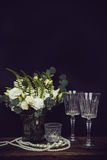 Bouquet of white flowers, pearl beads and wine glasses on a blac Stock Photography
