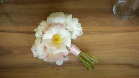 Bouquet of white flowers tied with a pink ribbon on a wooden table. Slider shot stock video footage