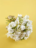 Bouquet of white flowers. Wedding bouquet of white flowers with ribbon on yellow background Royalty Free Stock Image