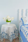 Bouquet of white hydrangea flowers on a side bed table in a coun Royalty Free Stock Image