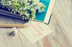 Bouquet of a white lilac on the open book, pencil and the white card with the inscription Good morning! Royalty Free Stock Photography