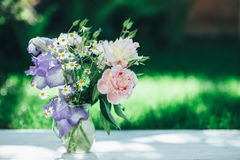 Bouquet of white peonies, chamomiles and iris flowers in glass vase. Summer background. Tinted photo Stock Photos