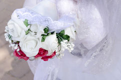 A bouquet of white and pink artificial roses in white dress Royalty Free Stock Images