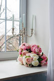 Bouquet of white and pink flowers with candles near the window. Stock Images