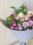 The bouquet of white and pink spray roses in gray floral paper Stock Image
