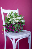 Bouquet of white and purple tulips on white chair Stock Images