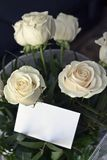 Bouquet of white roses and blank card to write a message Royalty Free Stock Image