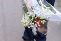 Bouquet of white roses close-up and blurred boys legs in the background stock photography