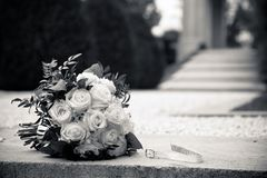 A bouquet of white roses on a granite. Black and white background royalty free stock image