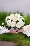 Bouquet of white roses in hand of groom and bride Stock Photo