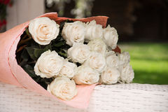Bouquet of white roses. A bouquet of white roses lies on a wicker table Stock Image