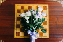Bouquet of white roses lying on chessboard. Isolated at wooden table background Royalty Free Stock Photo