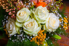 Bouquet with white roses. With other small flowers of different colors and green twigs royalty free stock image