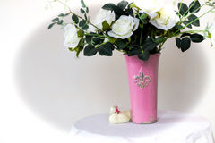 A bouquet of white roses in a vase. Placed on a table, which is covered with a cloth royalty free stock image