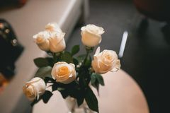 Bouquet of white roses on a white wooden table. Flower arrangement close-up. Modern interior design stock photos