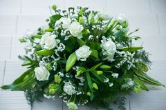 Big bouquet of white roses, yellow daffodils, greenery and lotuses Stock Photo