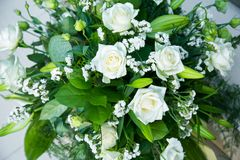 Big bouquet of white roses, yellow daffodils, greenery and lotuses Royalty Free Stock Photos