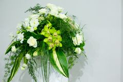 A bouquet of white roses, yellow daffodils, greenery and lotuses stands in a vase on a marble stand Stock Image