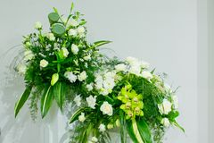A bouquet of white roses, yellow daffodils, greenery and lotuses stands in a vase on a marble stand Royalty Free Stock Images